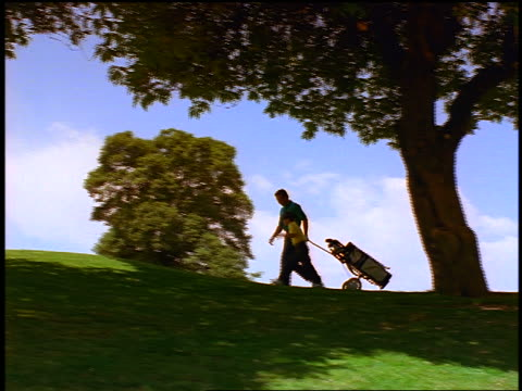 low angle wide shot PAN man + boy pulling golf bag walk on hilltop on golf course / man shows golf club to boy