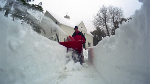 low angle wide shot man clearing path with snowblower towards camera / house in background / Maine