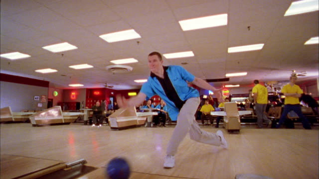 vídeos de stock, filmes e b-roll de low angle wide shot man in blue jersey stepping to lane and releasing bowling ball / cheering + clapping - cancha de jogo de boliche