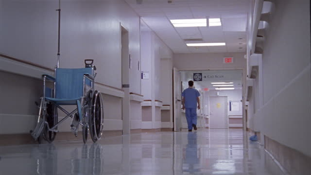 vidéos et rushes de low angle wide shot man in scrubs walking in hospital hallway / surgeon leaning against wall in hallway and resting - s'appuyant