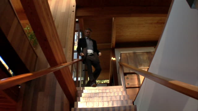 Low angle wide shot man in suit walking down stairs in modern building