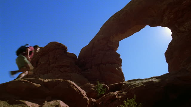 vídeos de stock e filmes b-roll de low angle wide shot man jumping across boulders and hiking by natural rock arch / arches national park, utah - ecoturismo