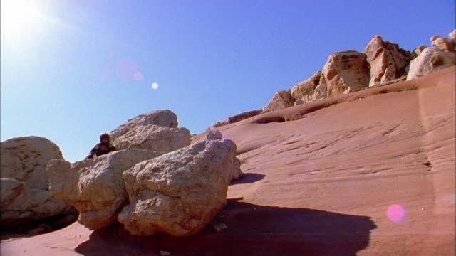 Low angle wide shot man jumping mountain bike over rock