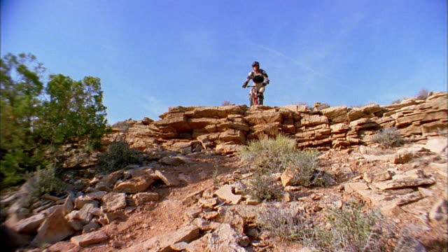 Low angle wide shot man jumping on mountain bike over rock shelf and riding downhill past CAM