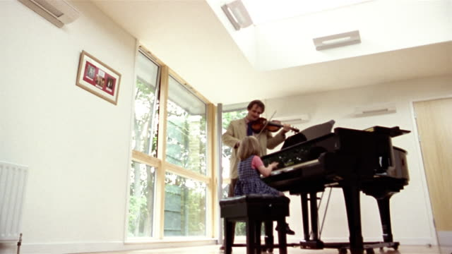 Low angle wide shot man playing violin as his daughter plays piano