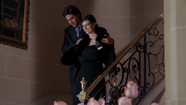 Low angle wide shot man putting fur stole on woman's shoulders and escorting down marble staircase