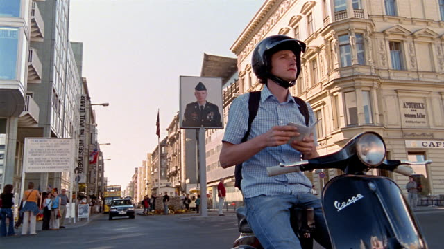 Low angle wide shot man riding Vespa in street / stopping to check map and riding off / Berlin, Germany