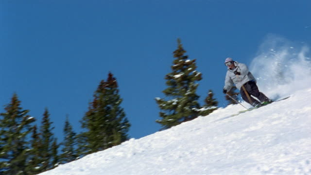 low angle wide shot man skiing down slope / breckenridge, colorado - ski jacket stock videos & royalty-free footage