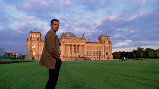 low angle wide shot man standing with back to cam looking at the reichstag / turning around looking at cam / berlin - 30 39 years stock videos & royalty-free footage