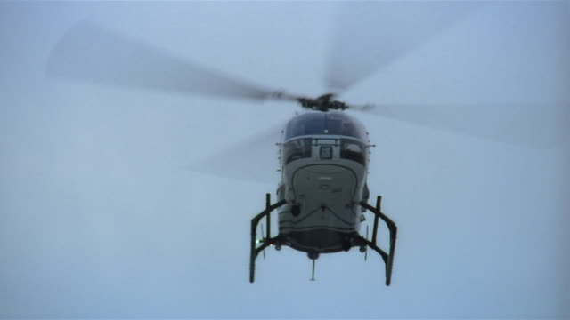 low angle wide shot medivac helicopter landing in hospital parking lot - hubschrauber stock-videos und b-roll-filmmaterial