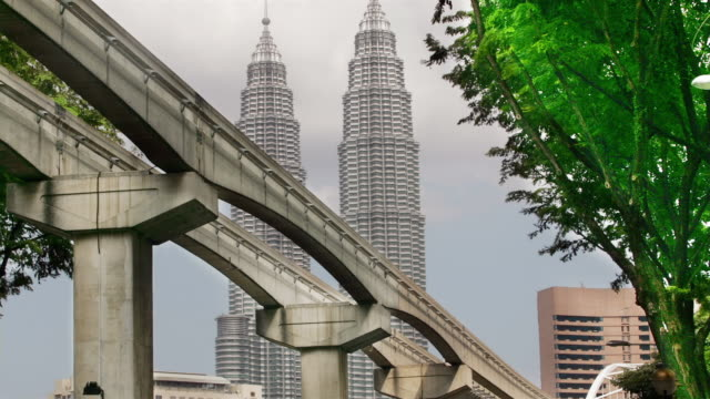 low angle wide shot monorail going by with petronas towers in background/ kuala lumpur - kuala lumpur stock videos & royalty-free footage