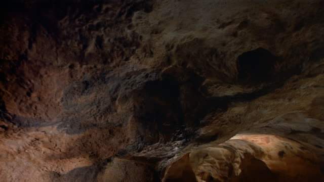 low angle wide shot moving through cave with paintings on ceiling / france - cave stock videos & royalty-free footage