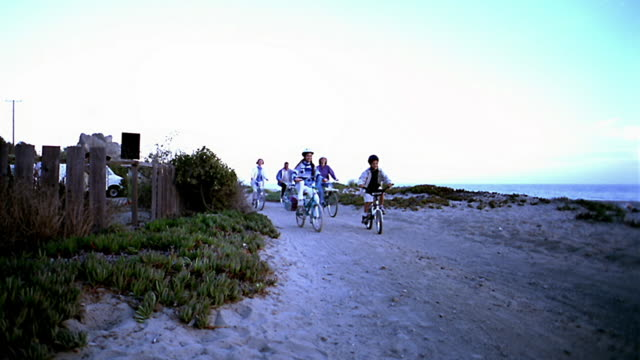 low angle wide shot multi-generational family riding bicycles by beach with children wearing helmets / california - familie mit mehreren generationen stock-videos und b-roll-filmmaterial