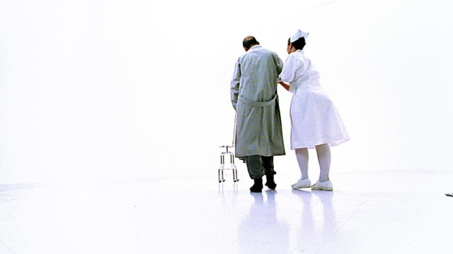 vídeos de stock e filmes b-roll de low angle wide shot nurse walking mental patient to stool in middle of white room - super exposto