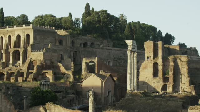 Low angle wide shot of statues and pillars in ancient ruins / Rome, Italy