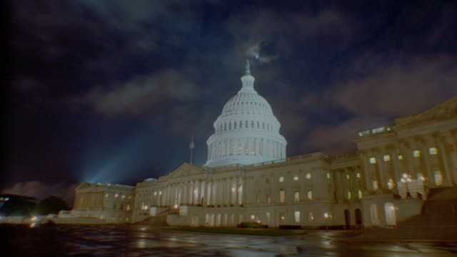 low angle wide shot of time lapse clouds over Capitol Building at night / Washington DC