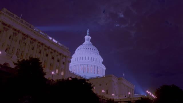 vídeos y material grabado en eventos de stock de low angle wide shot of time lapse clouds over capitol building at night / washington dc - edificio gubernamental