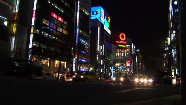 low angle wide shot of traffic passing san'ai dream center lit up at night / tokyo - 2005年点の映像素材/bロール