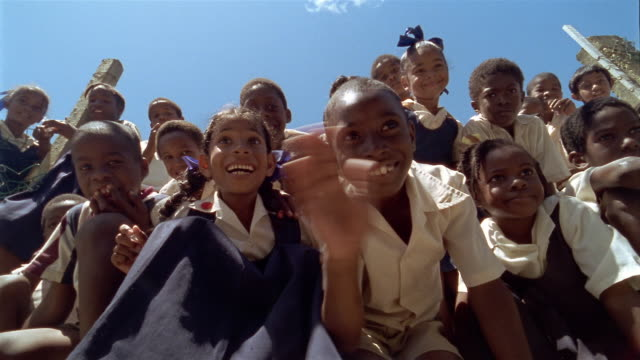 Low angle wide shot pan children in school uniforms smiling and waving at CAM