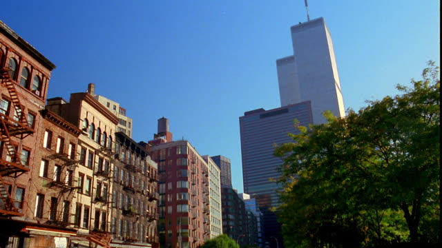 low angle wide shot pan from world trade center to apartment buildings on greenwich street / downtown manhattan, new york city - world trade center manhattan video stock e b–roll