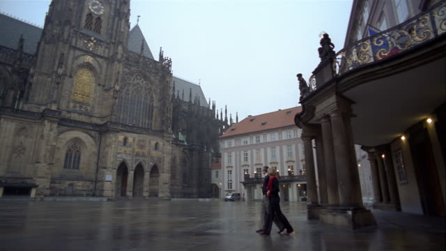 low angle wide shot pan man and woman walking through courtyard at prague castle / prague - hradcany square stock videos and b-roll footage