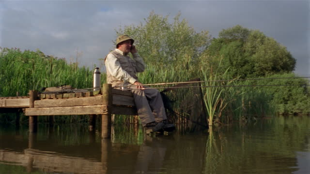 low angle wide shot pan man fishing at end of jetty talking on cell phone with net and rod hanging over edge - one mature man only stock videos & royalty-free footage
