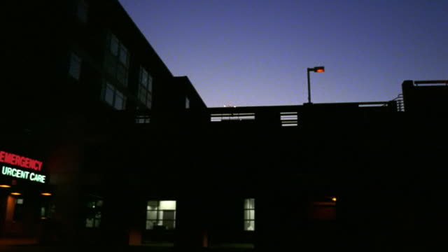 Low angle wide shot pan silhouetted hospital building with entrance to emergency room at dusk / Tucson, Arizona