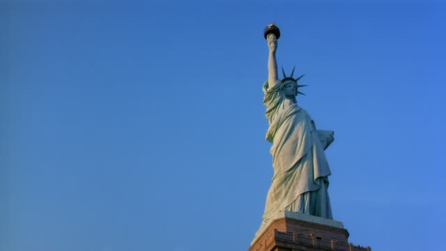 low angle wide shot pan statue of liberty against clear blue sky / new york city - statue of liberty stock videos and b-roll footage