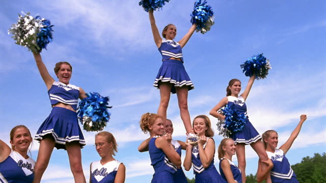 low angle wide shot pan teen female cheerleaders in uniform cheering in four-person pyramids on field - cheerleader stock videos and b-roll footage