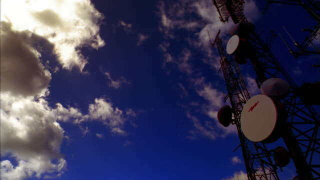 low angle wide shot pan time lapse clouds moving over broadcast towers - microwave tower stock videos and b-roll footage