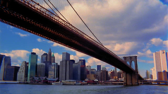 Low angle wide shot pan time lapse clouds moving over Brooklyn Bridge