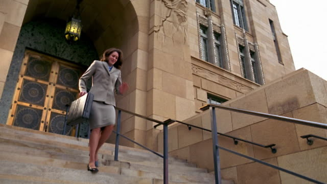 Low angle wide shot pan woman in suit running down stairs to court smiling