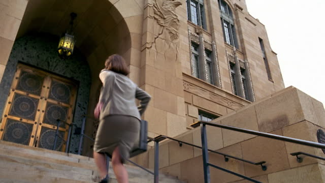 vidéos et rushes de low angle wide shot pan woman in suit running up stairs to court building - marches et escaliers