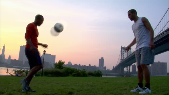 vídeos de stock, filmes e b-roll de low angle wide shot panning two men passing soccer ball back and forth in park with manhattan bridge in background / dumbo, brooklyn, new york - passe de bola
