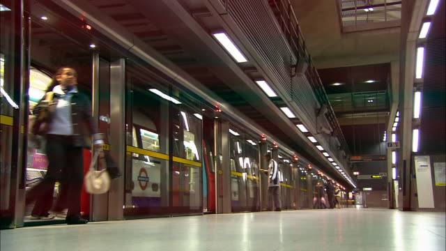 low angle wide shot passengers getting off train at canary wharf tube station / london underground / london - london underground stock videos & royalty-free footage