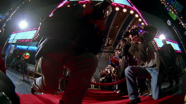 Low angle wide shot photographers and groupies on either side of red carpet