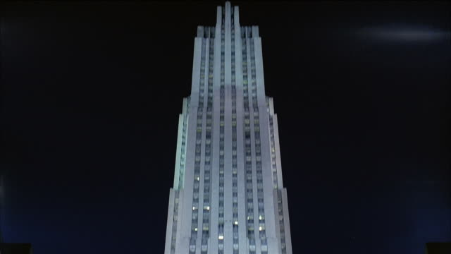 low angle wide shot rockefeller center at night / tilt down christmas tree and decorations lit up in plaza / new york city - rockefeller center stock videos & royalty-free footage
