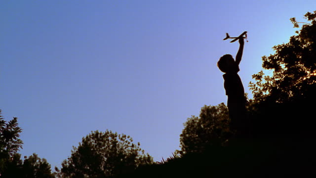 canted low angle wide shot silhouette boy spinning in circles holding toy airplane above head - modellflugzeug stock-videos und b-roll-filmmaterial