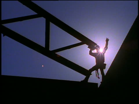 low angle wide shot silhouetted construction worker guiding beams - unknown gender stock videos & royalty-free footage