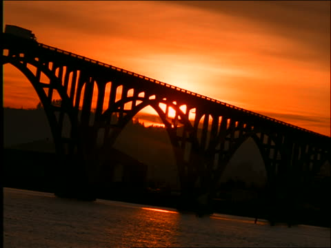 canted low angle wide shot silhouetted truck driving on bridge at sunset / yaquina bay, newport, oregon - newport oregon stock videos & royalty-free footage
