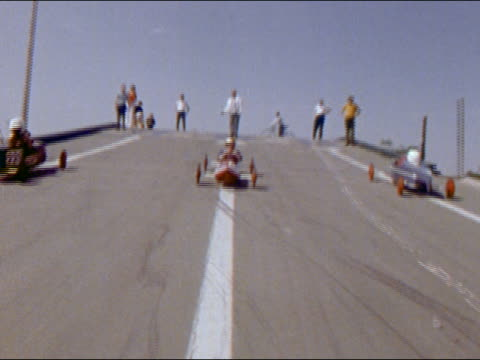 1970 low angle wide shot soapbox cars racing down street incline toward cam - go cart stock videos & royalty-free footage
