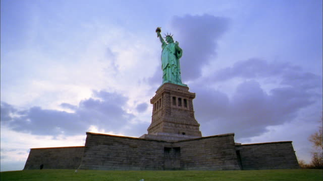 vídeos de stock, filmes e b-roll de low angle wide shot statue of liberty on pedestal - estátua