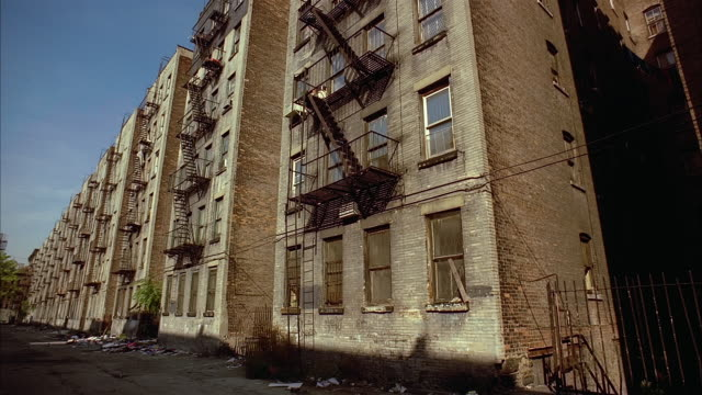 low angle wide shot tenement buildings with boarded up windows along alleyway in harlem / new york city - 1990 stock videos & royalty-free footage