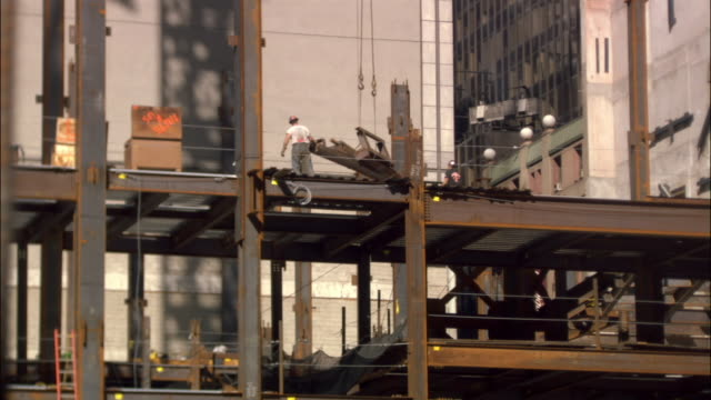 low angle wide shot tilt down crane moving girder onto construction frame/ new york city - 桁橋点の映像素材/bロール