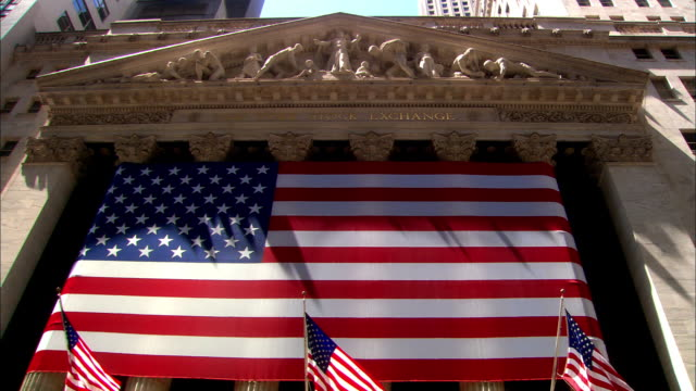 low angle wide shot tilt down large american flag on new york city stock exchange - new york stock exchange stock videos & royalty-free footage