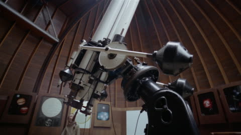 low angle wide shot tilt down roof retracting as girl enters observatory / girl looking through telescope - astronomi bildbanksvideor och videomaterial från bakom kulisserna