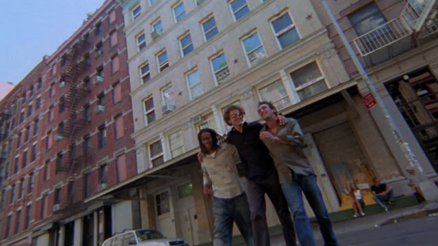 low angle wide shot tilt up three young men crossing street / tribeca, nyc - tribeca stock videos & royalty-free footage