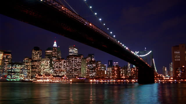 Low angle wide shot time lapse boats on East River and under Brooklyn Bridge with downtown Manhattan lit up at night / NYC