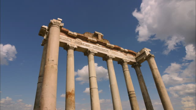 Low angle wide shot time lapse clouds in blue sky passing behind Saturn's temple at Roman Forum / Rome
