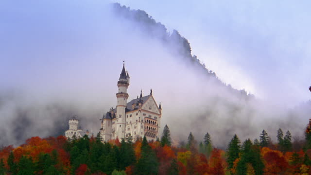 Low angle wide shot time lapse clouds moving behind Neuschwanstein Castle / Bavaria, Germany